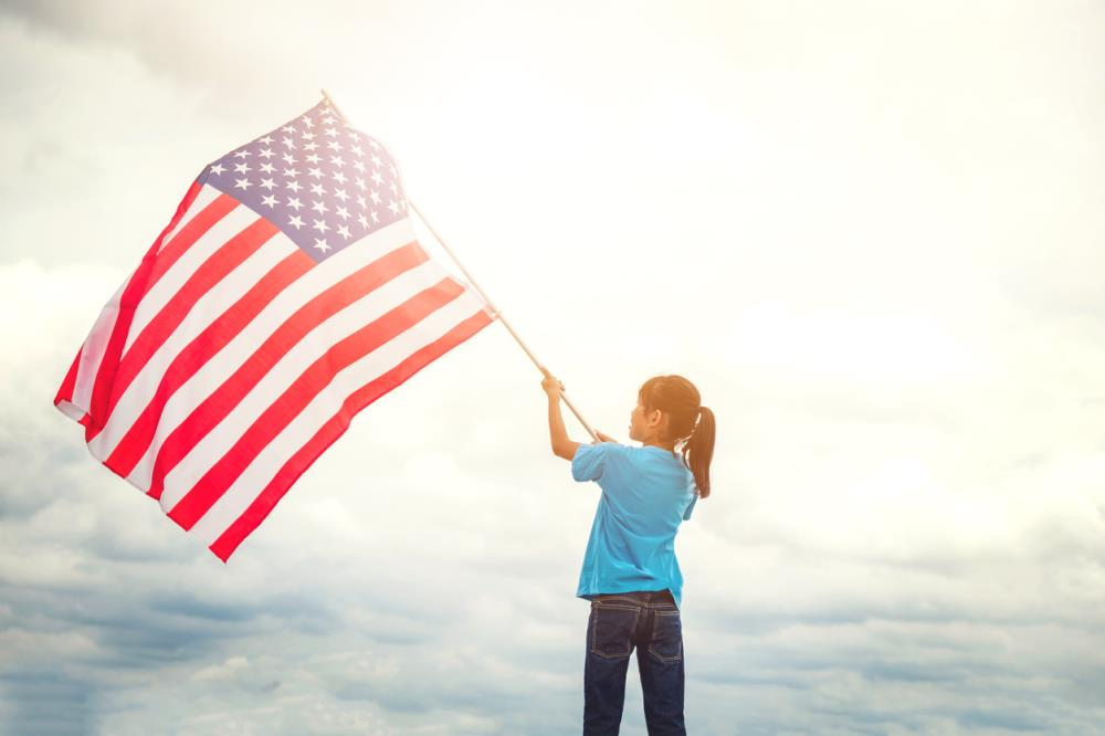 girl waving large American flag